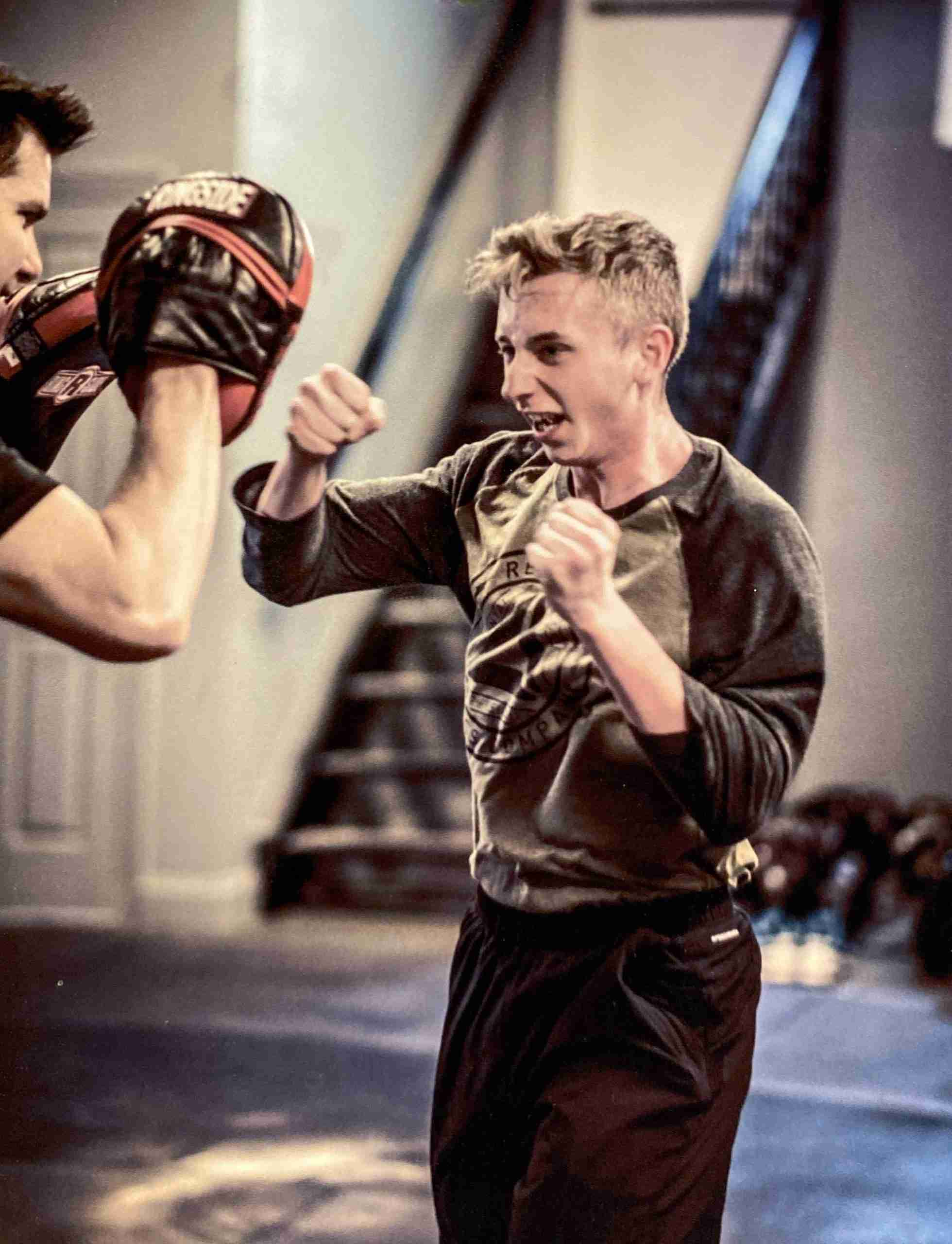 Matt holding pads for a young man punching